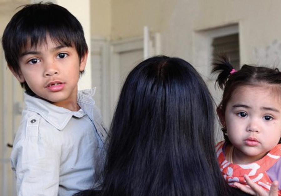 A Filipino mother holds her two children