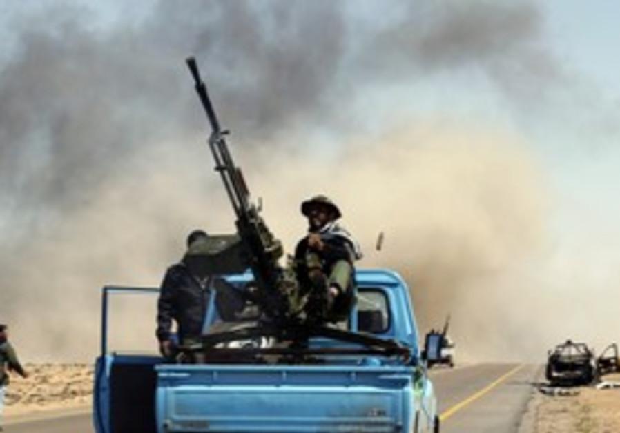 A rebel fires an anti-aircraft gun near Brega.
