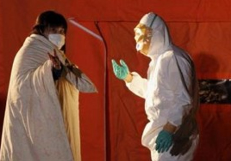 Japan official speaks to woman in protective gear