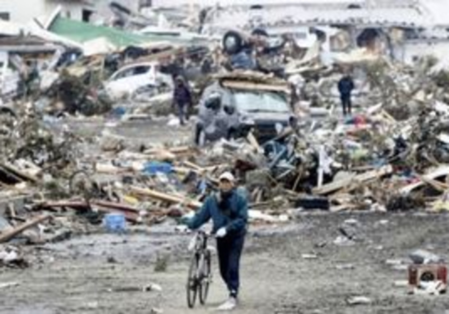A resident walks past destruction in Sendai, Japan