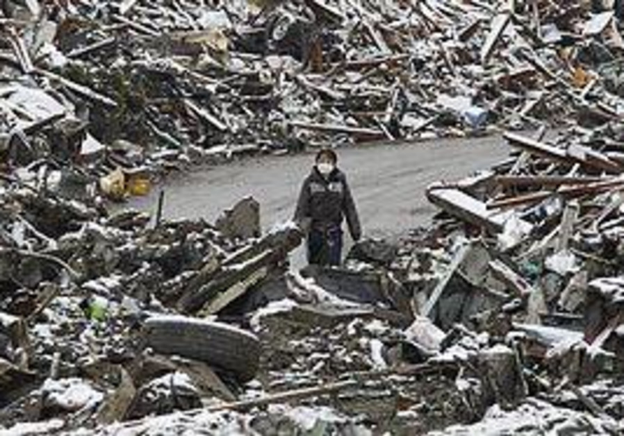A woman walks past snow-covered rubble in Japan