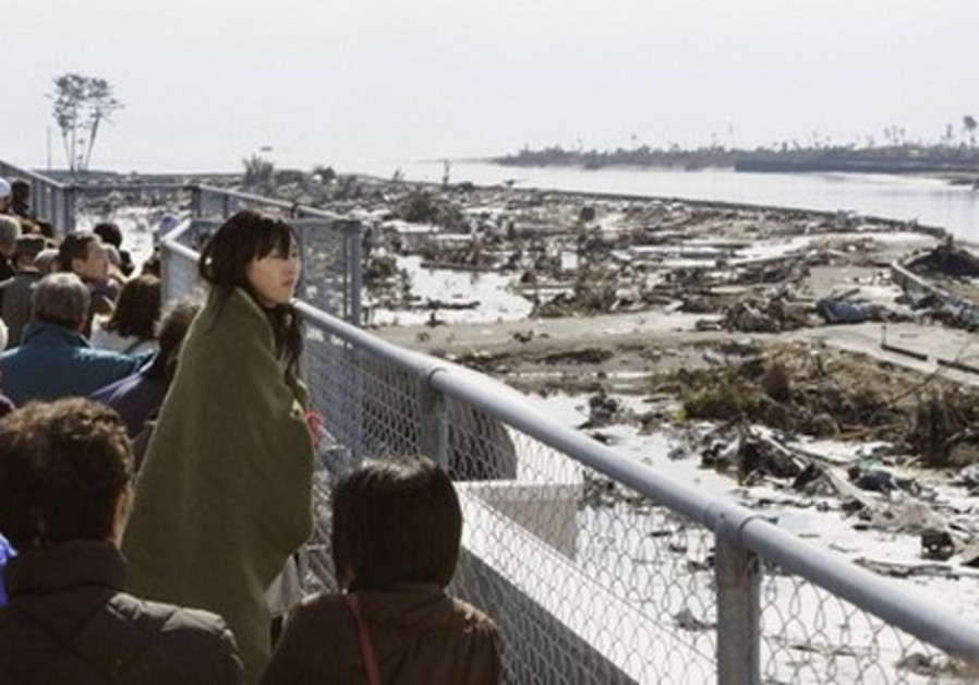 Japanese woman looks on the damage by the tusnami