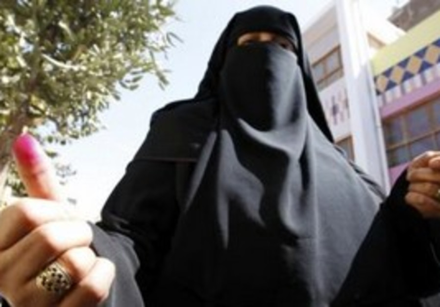 Woman shows inked finger after voting in Egypt