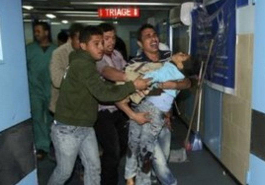 A Palestinian child is carried into Gaza hospital