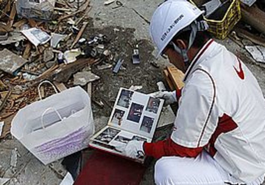 A Japanese man looks at a photo album in the rubbl