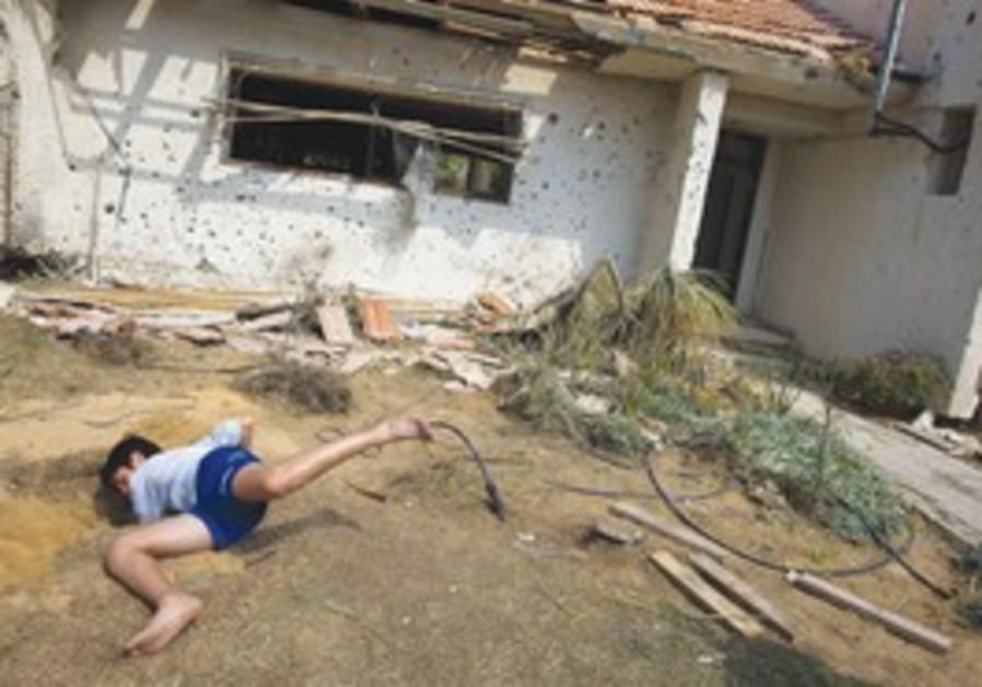 Boy looks for shrapnel after rocket fired