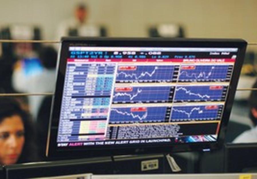 Traders look at screens at a bank in Lisbon, Weds.