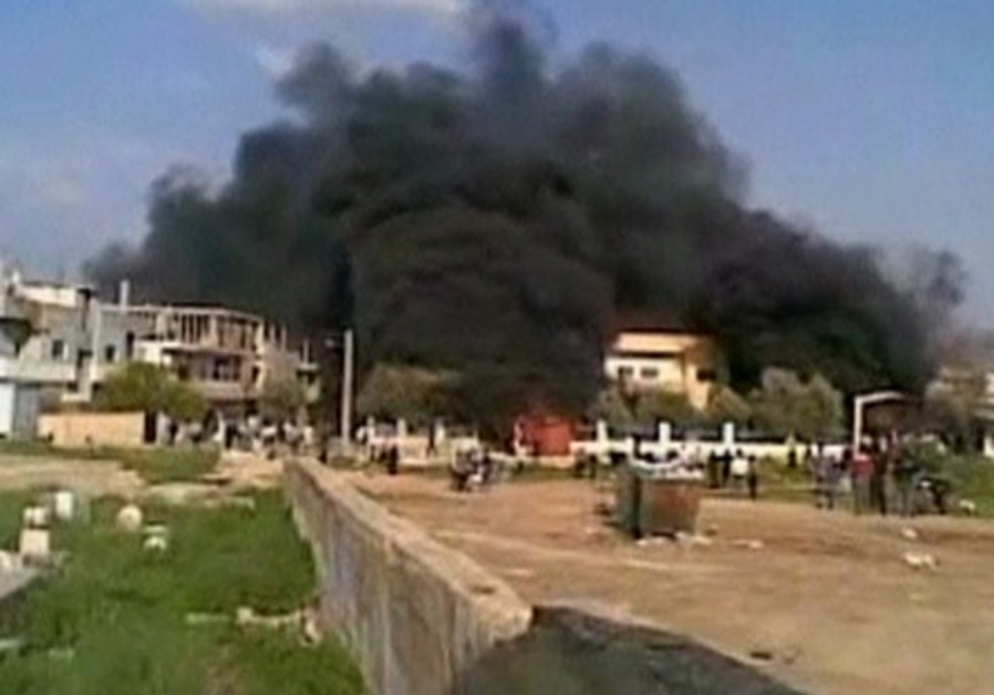 Smoke rises from a burning building in Deraa