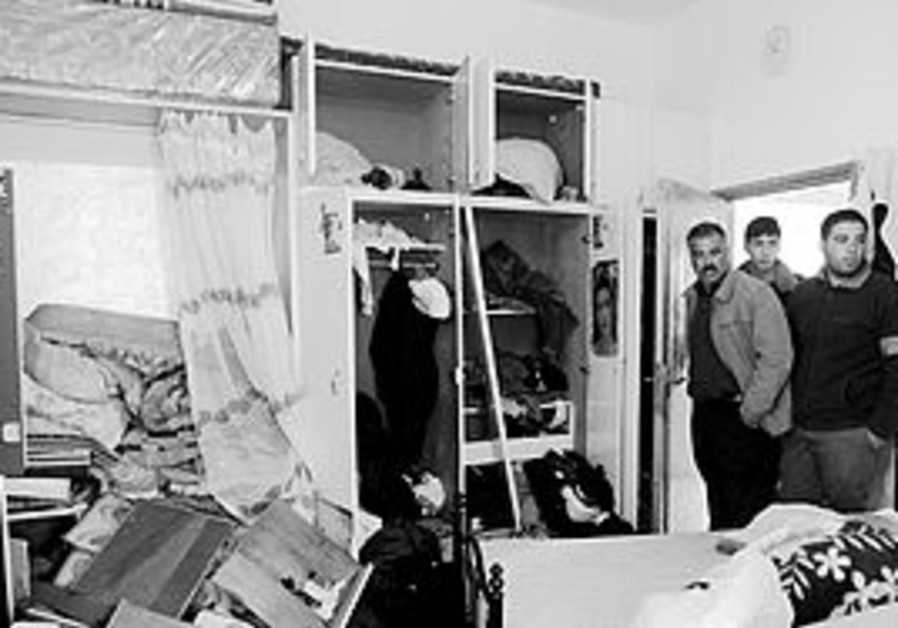 PALESTINIANS INSPECT damage inside their home