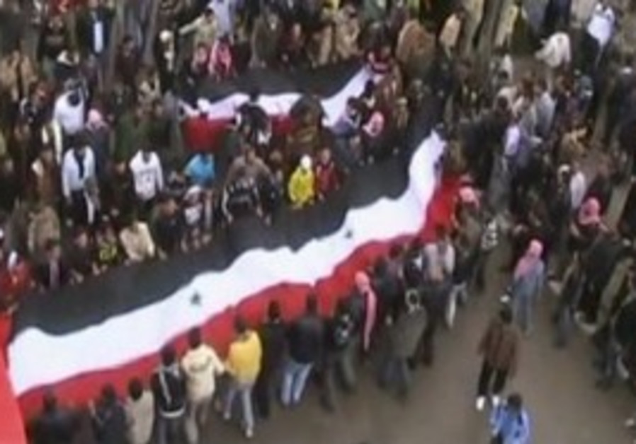 Syrian protesters in Deraa hoisting large flag
