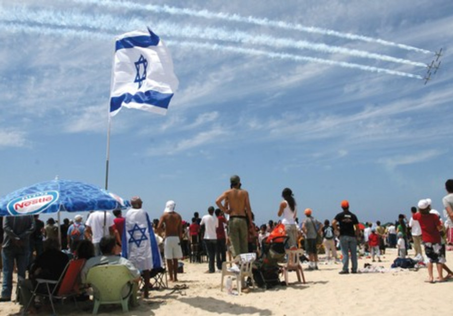 Crowds watch and Independence Day air show.