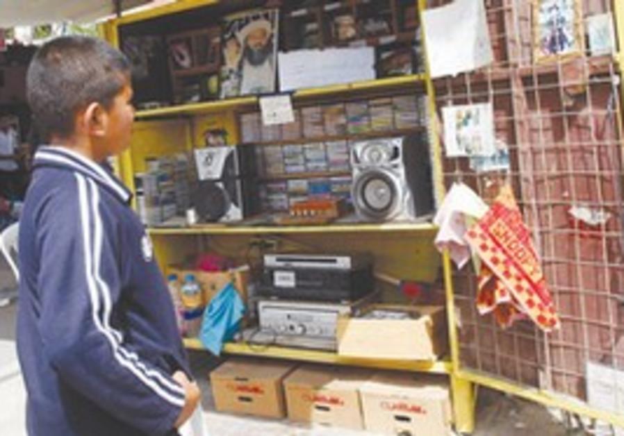A Palestinian boy looks at a photo of bin Laden.