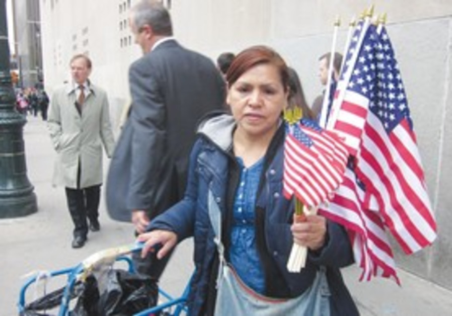 A woman hawks American flags on an NY street, Mon.