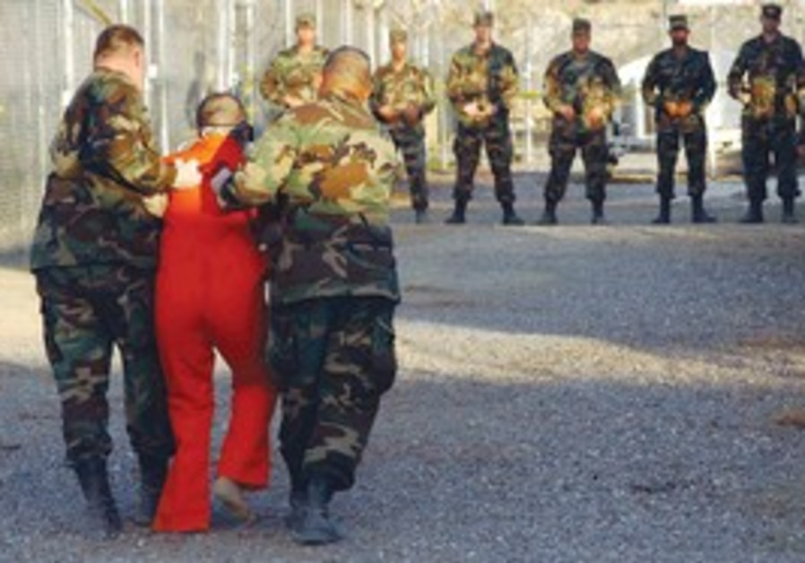 A detainee is escorted to his cell at Guantanamo.