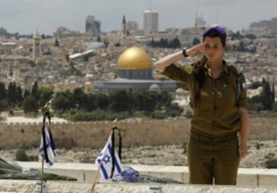 Israeli soldier salutes soldier's grave in J'lem.