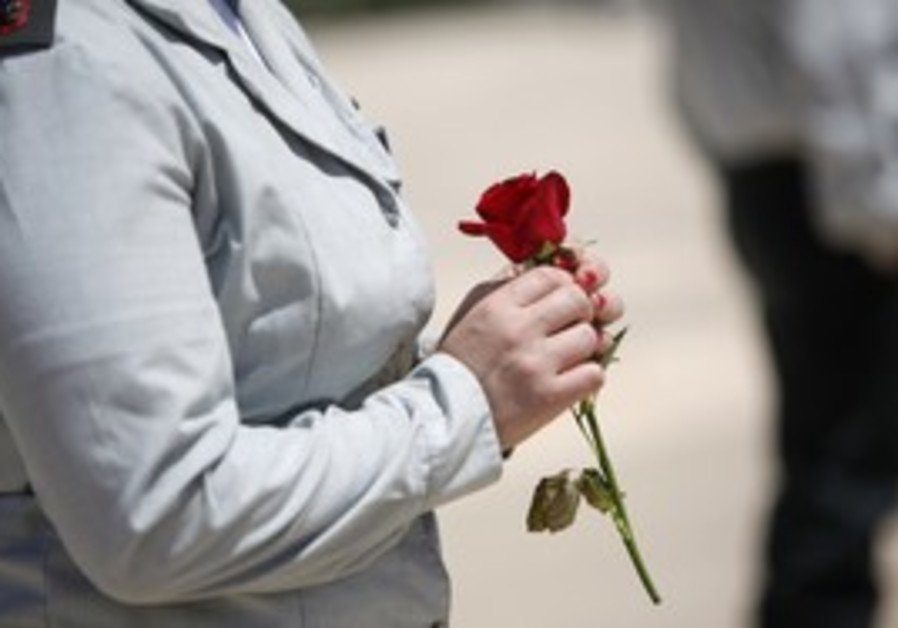 Israeli soldier holds a rose for Remembrance Day