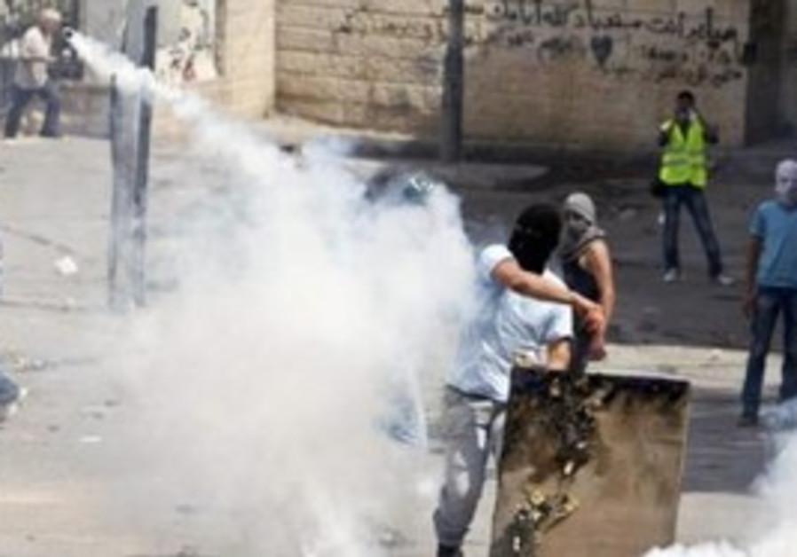 Arab throws back tear gas canister in Silwan