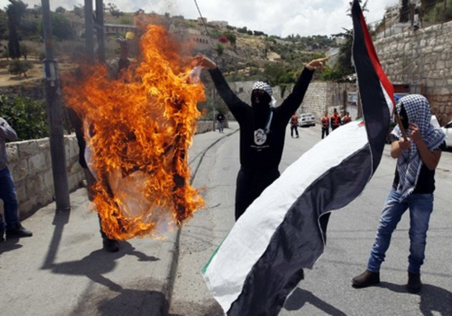 Palestinians burning a flag during Silwan clashes