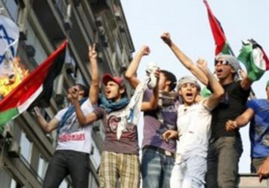 Egyptian protesters burn an Israeli flag.
