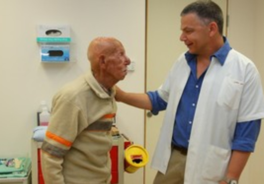 MEIR KORNER stands with senior plastic surgeon