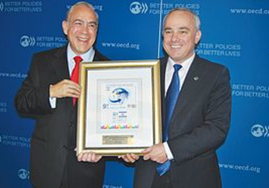 Yuval Steinitz and Angel Gurria with stamp.