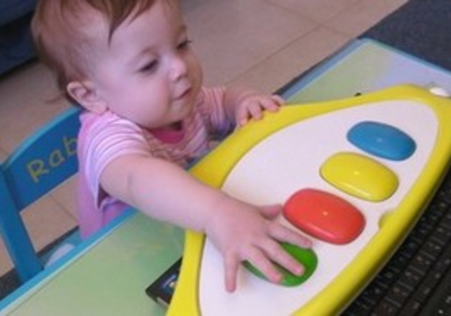 A baby plays with specially designed keyboard
