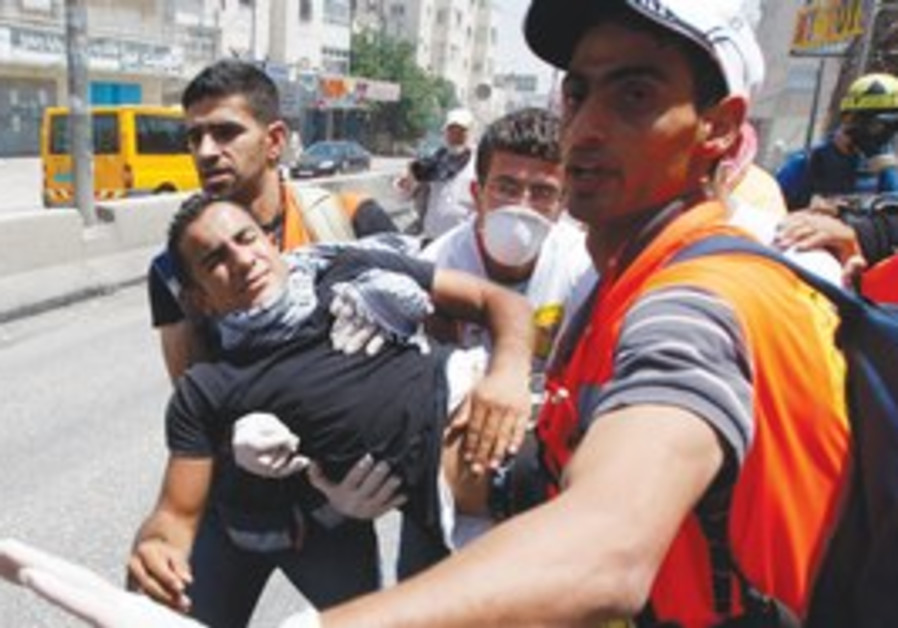 Medics carry injured man near Kalandiya checkpoint