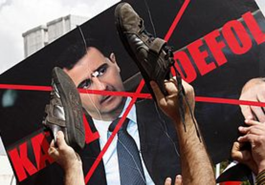 Protesters with a defaced poster of Assad
