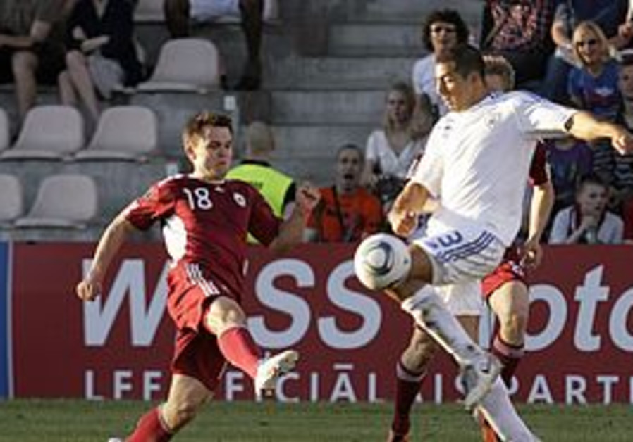 Tal Ben Haim (R) of Israel fights for the ball wit
