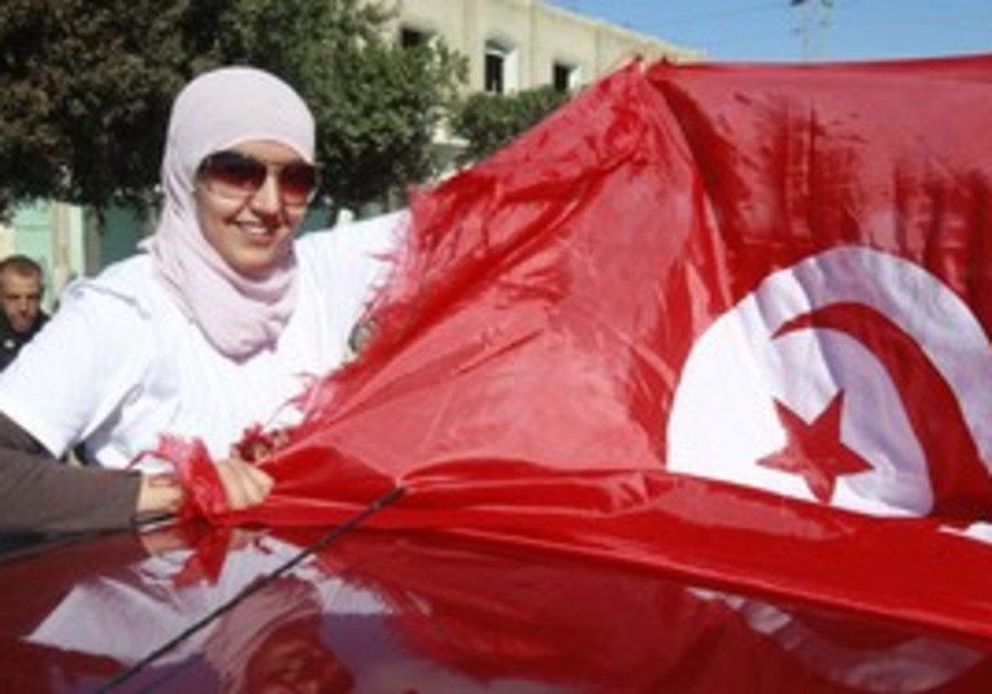 A Tunisian woman holds the national flag.
