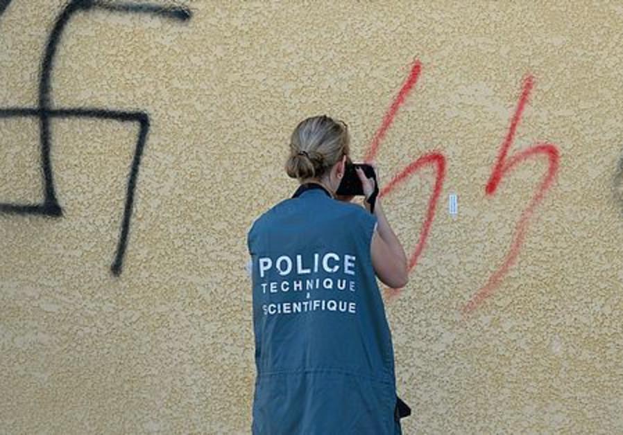 A policewoman photographs anti-Semitic graffiti