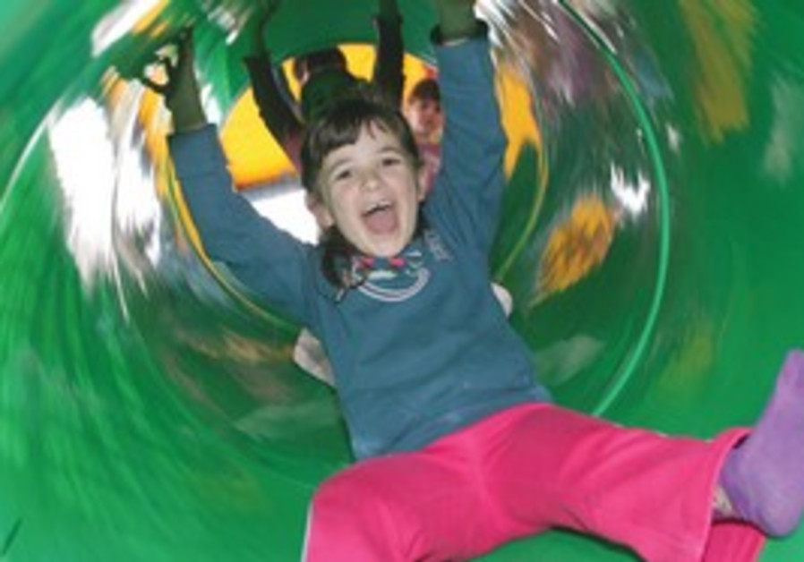 YOUNG GIRL enjoys a ride down a slide