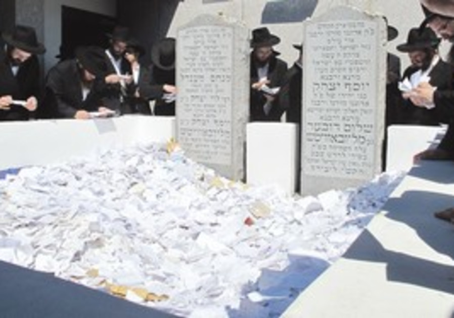 Scraps of paper at Rabbi Schneerson's grave