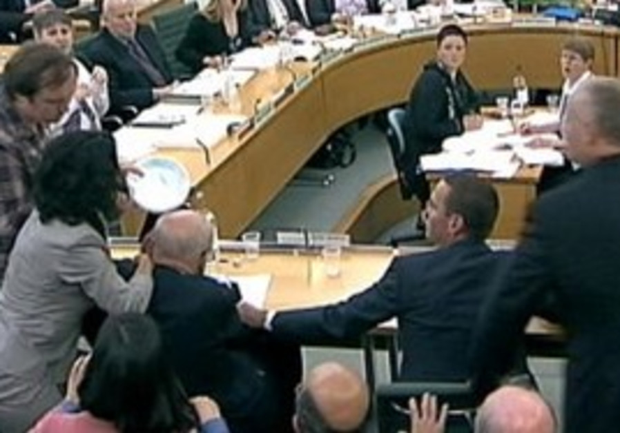Man tries to attack Rupert Murdoch during hearing.