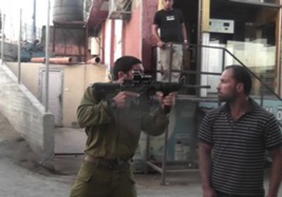 IDF officer points gun in Palestinian's face.
