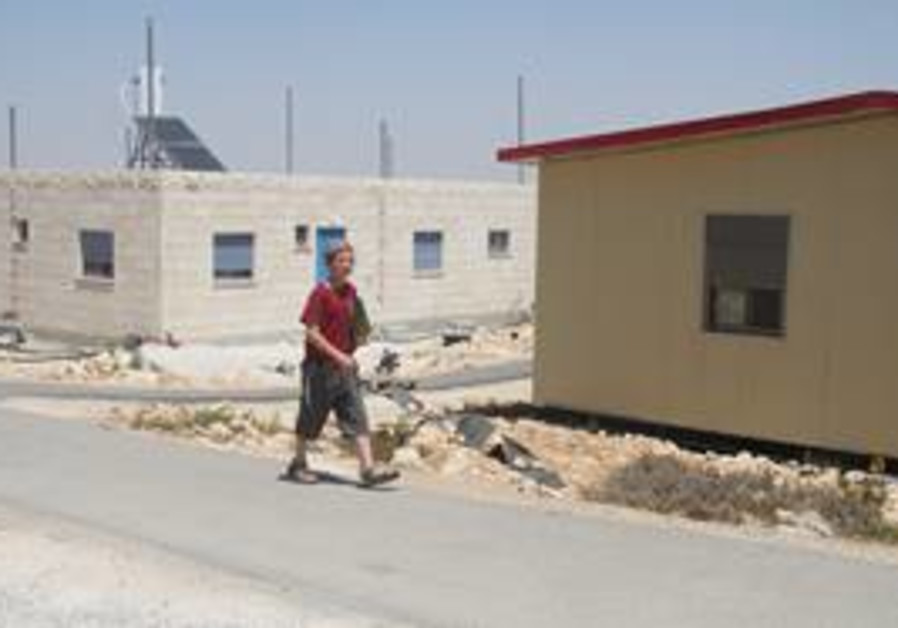Boy walks past homes in W. Bank outpost of Migron