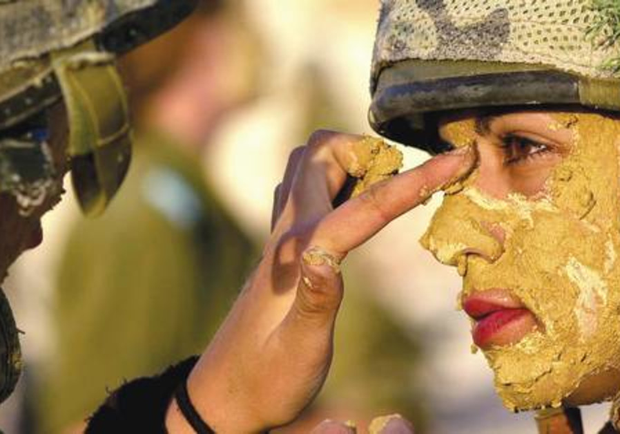 A female IDF soldier paints a comrade with mud.