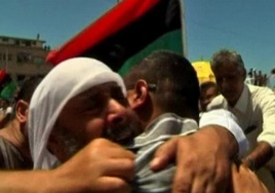 Libyans attend funeral for slain rebel leader.
