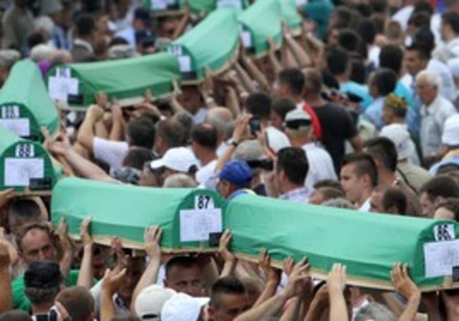 Bosnian Muslims carry coffins during a mass burial