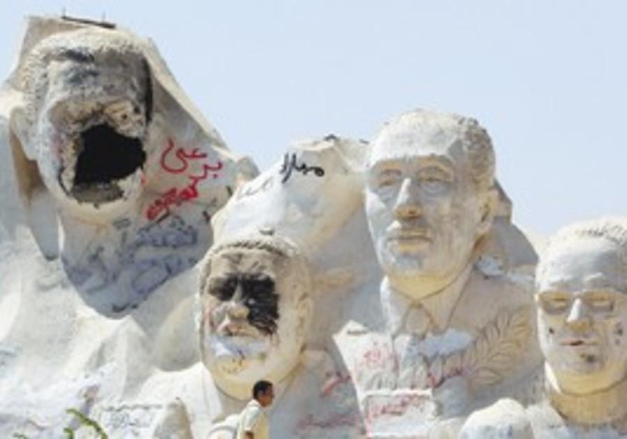 defaced Mubarak statue in Egypt