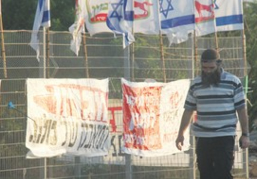 A man walks by protest signs in Migron outpost