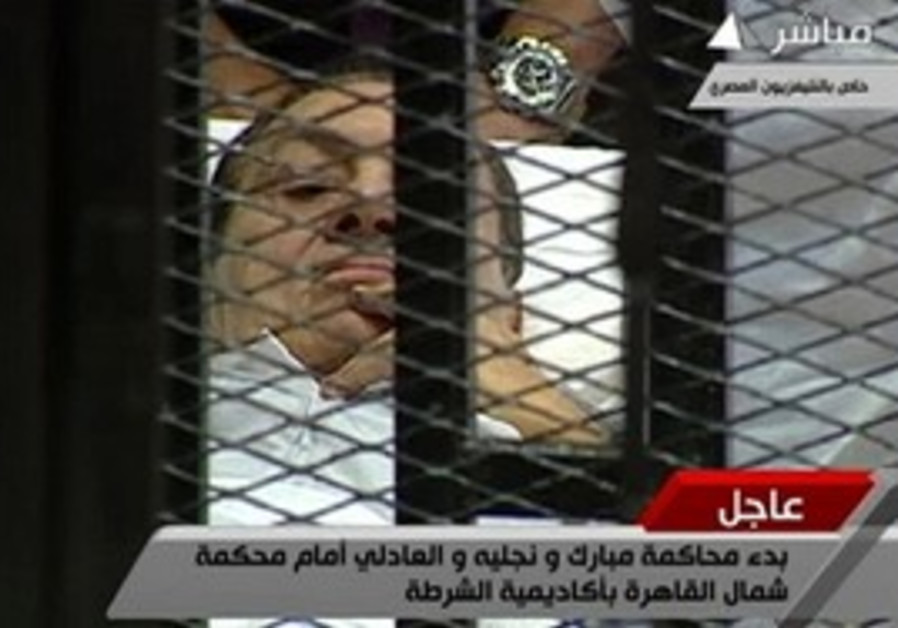 Hosni Mubarak in trial cage on stretcher