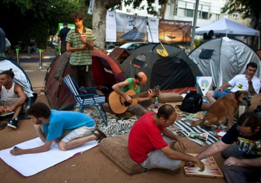Protesters sit outside tents in Tel Aviv