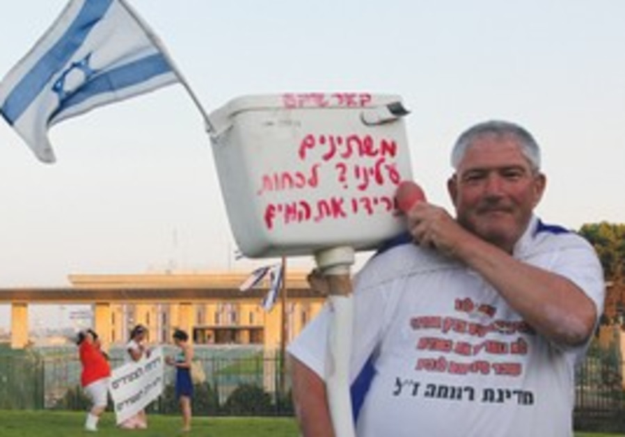 A protester outside the Knesset carries a toilet