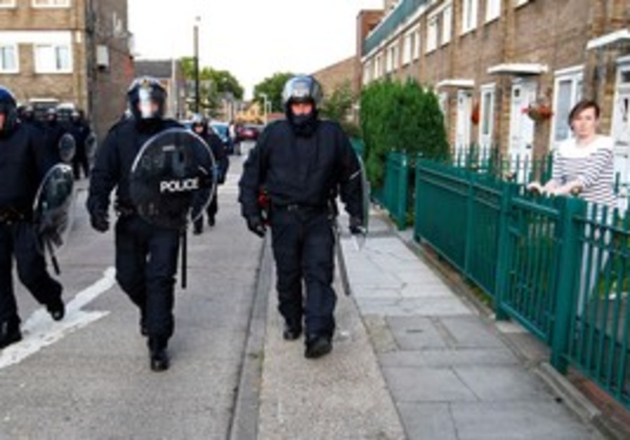 Riot police patrol through an estate in e. London