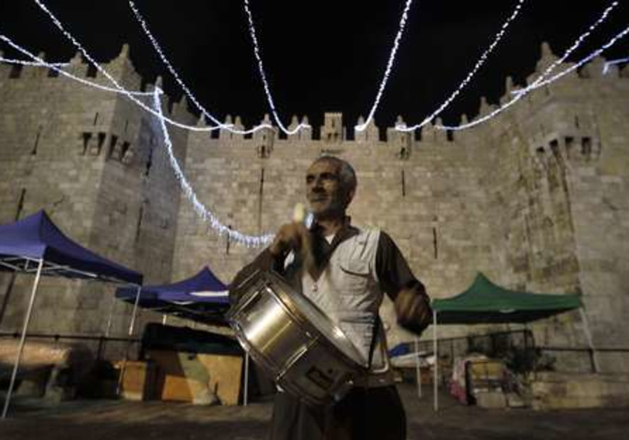 A Palestinian plays a drum at the Damscus gate