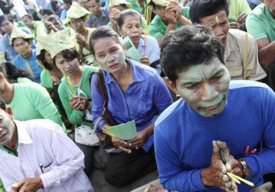 Protesters with painted faces pray in Cambodia