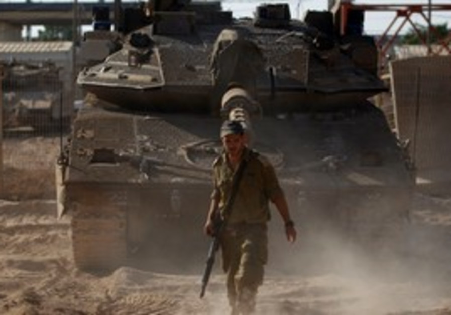 IDF soldier walks in front of tank on Gaza border