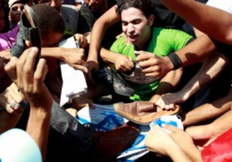 Egyptians hit Israeli flag in protest