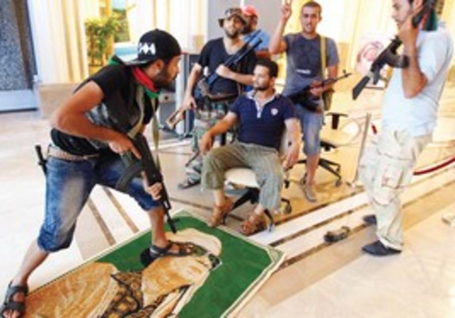 Rebels step on poster of Muammar Gaddafi